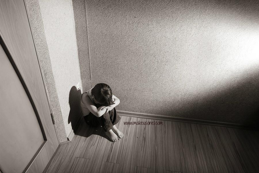 Child sitting in a room corner